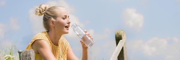 dame met glas water bij hek