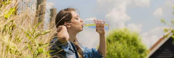 meisje drinkt kraanwater in de wei