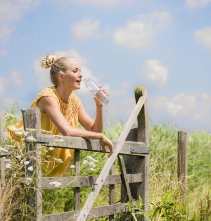 vrouw drinkt water bij hek
