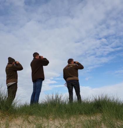 Boswachters met verrekijker in duinlandschap blauwe lucht