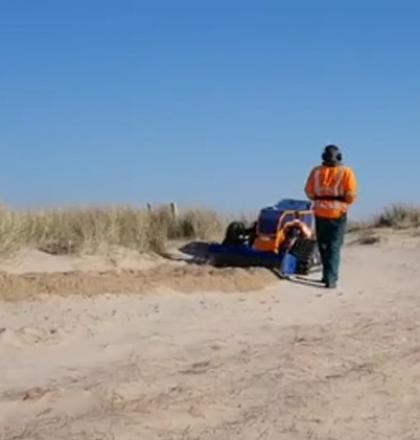 Man in oranje veiligheidsvest werkt in het duin met een kleine machine