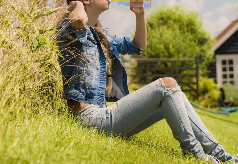 Vrouw met glas water in tuin