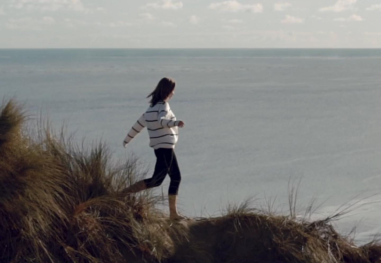 Vrouw loopt met blote voeten in het zand, de zon schijnt