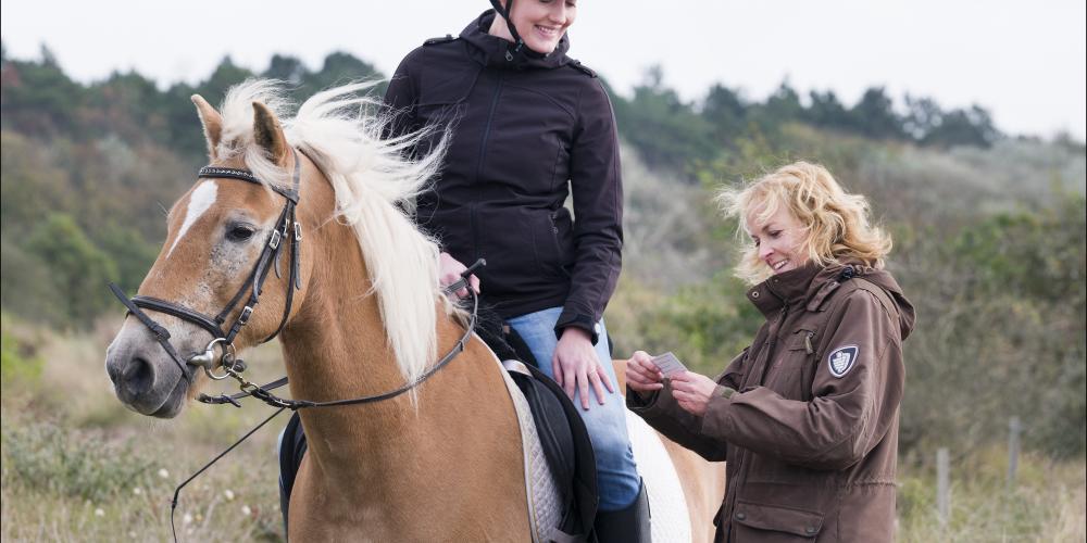 Boswachter controleert ruiter te paard op duinkaart