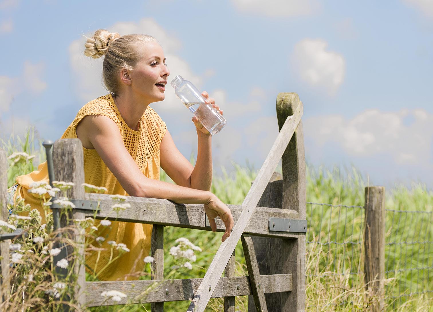 vrouw bij hek drinkt water